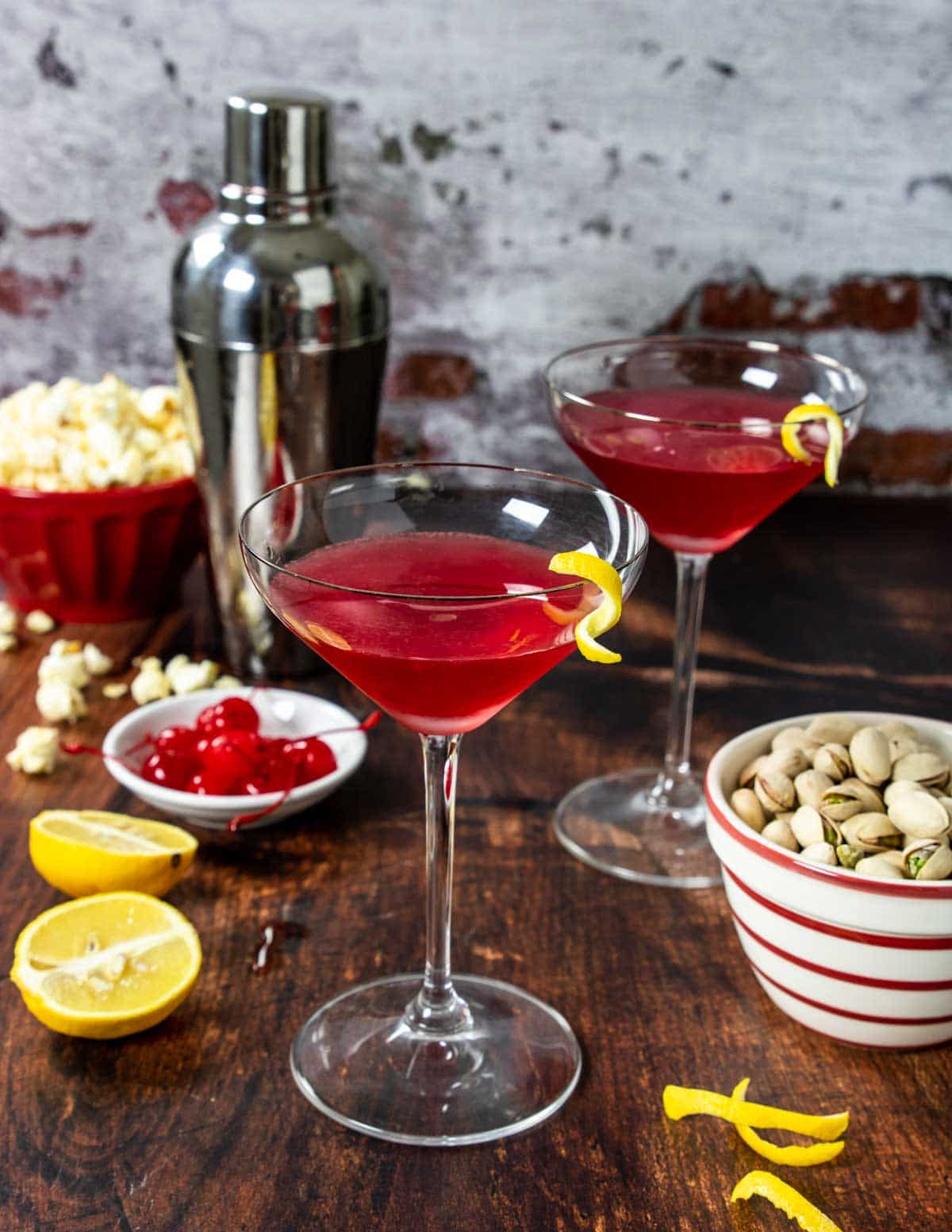a red martini cocktail on a table with snacks