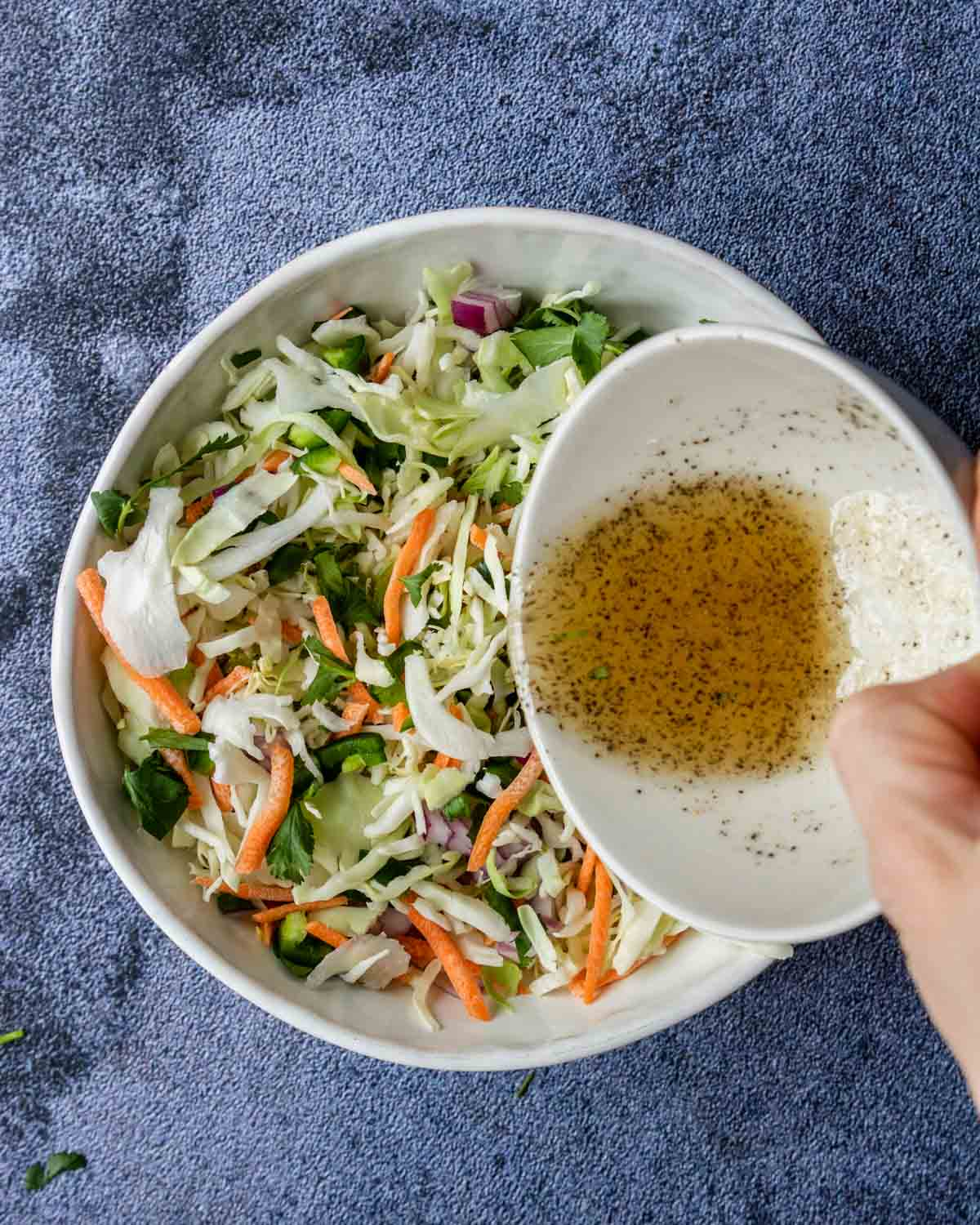 cilantro lime slaw with vinaigrette being poured over