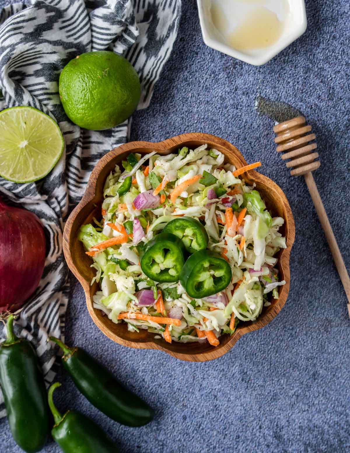 a bowl of cilantro lime slaw topped with jalapenos