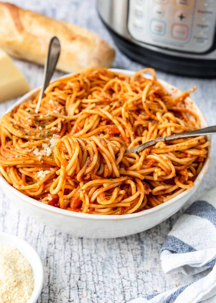 spaghetti with marinara in a bowl twirled on a fork, instant pot in the background