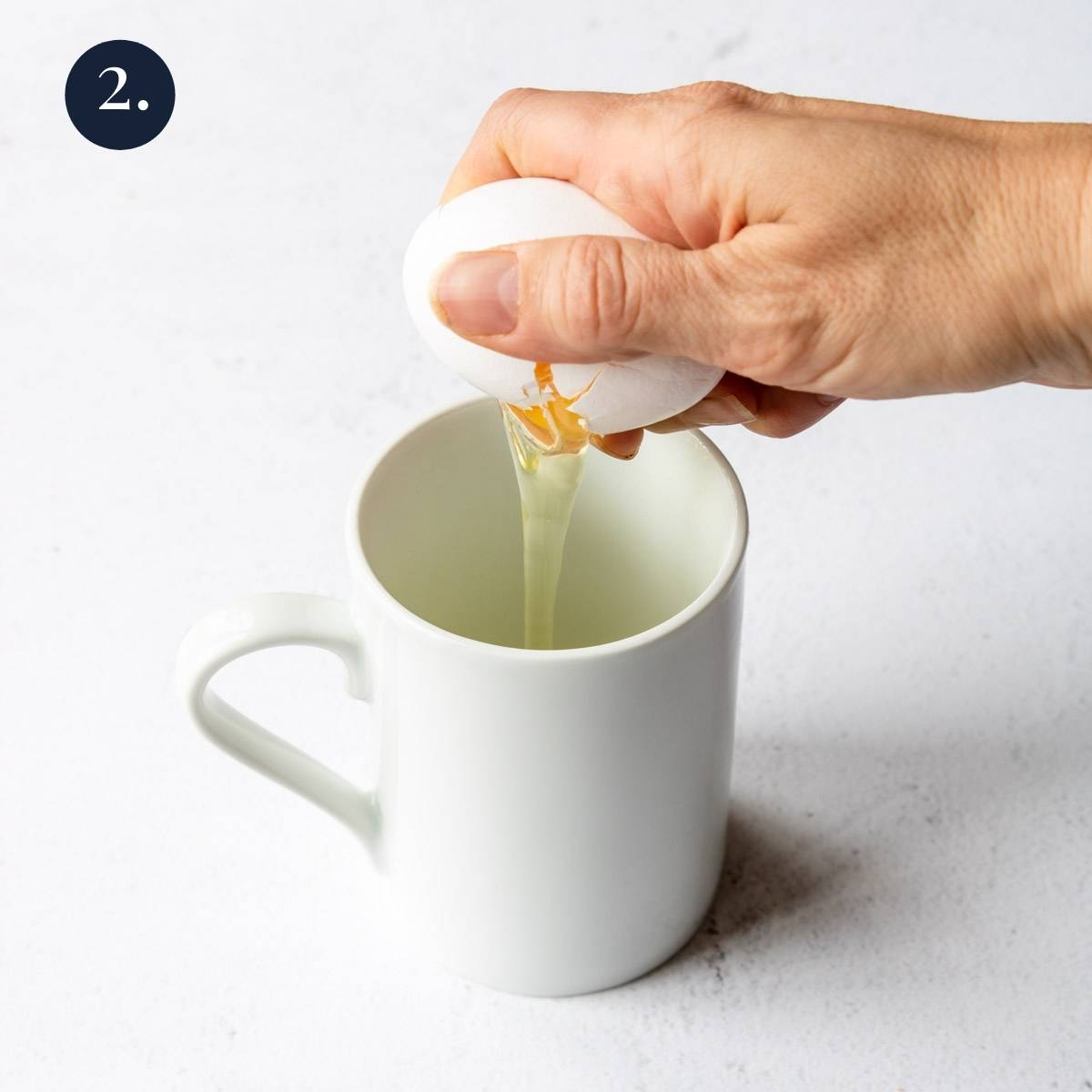 cracking an egg in a mug
