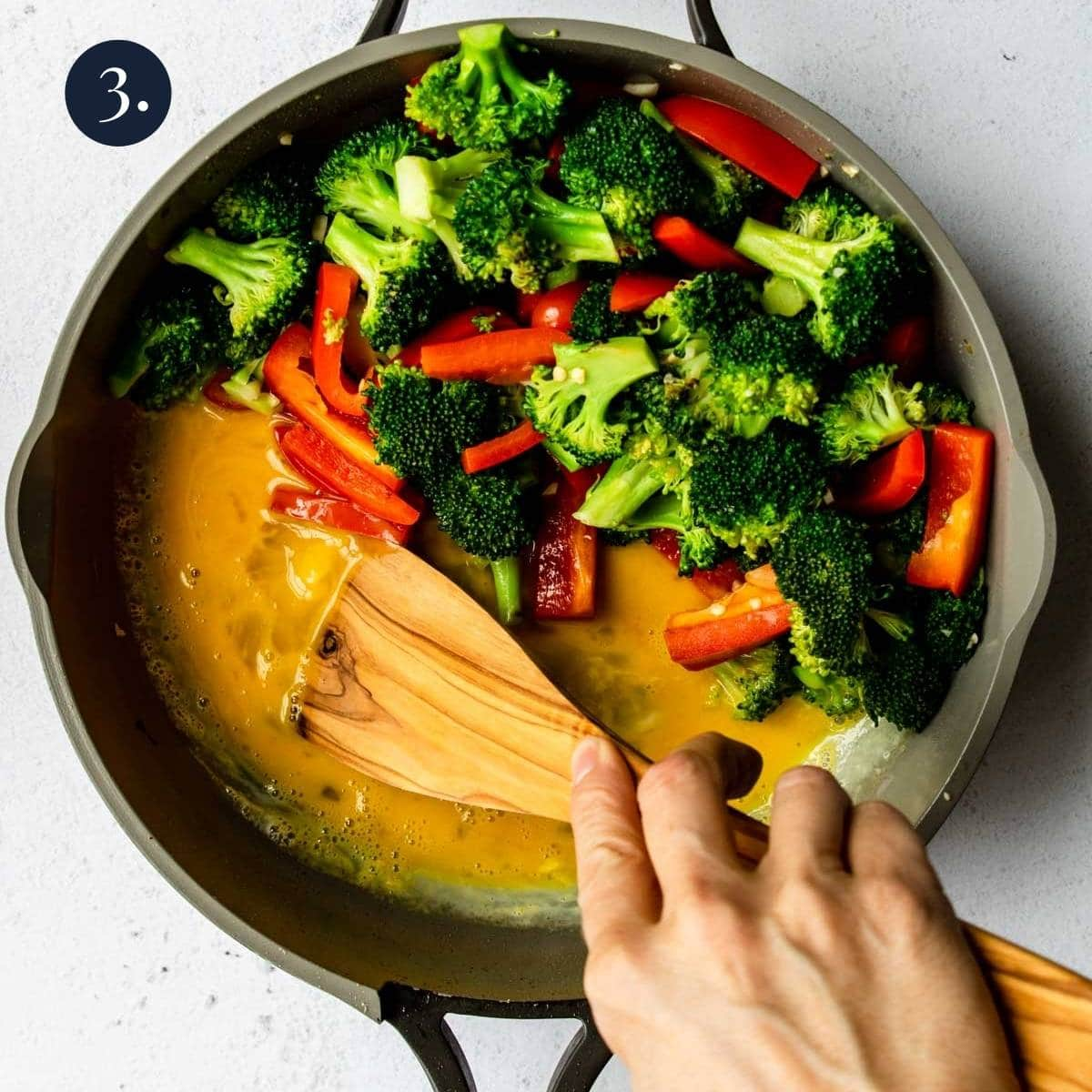 broccoli and red pepper to one side and cooking egg in the other side of the pan