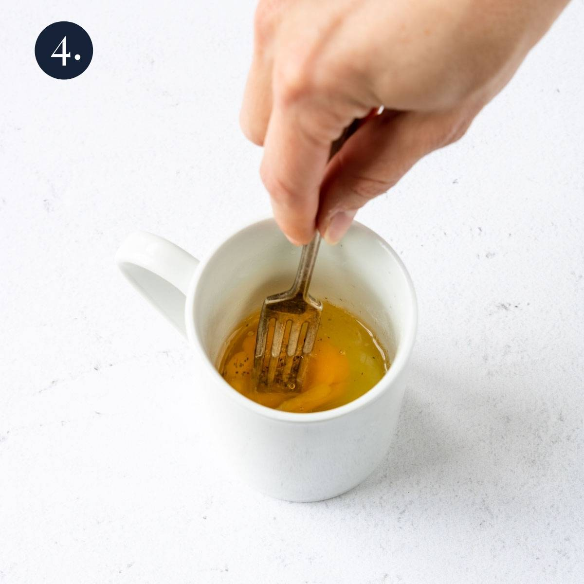 whisking eggs in a mug with a fork