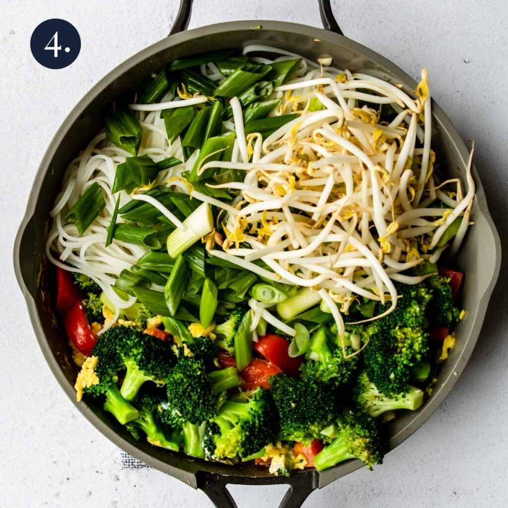 a skillet full of veggies and rice noodles