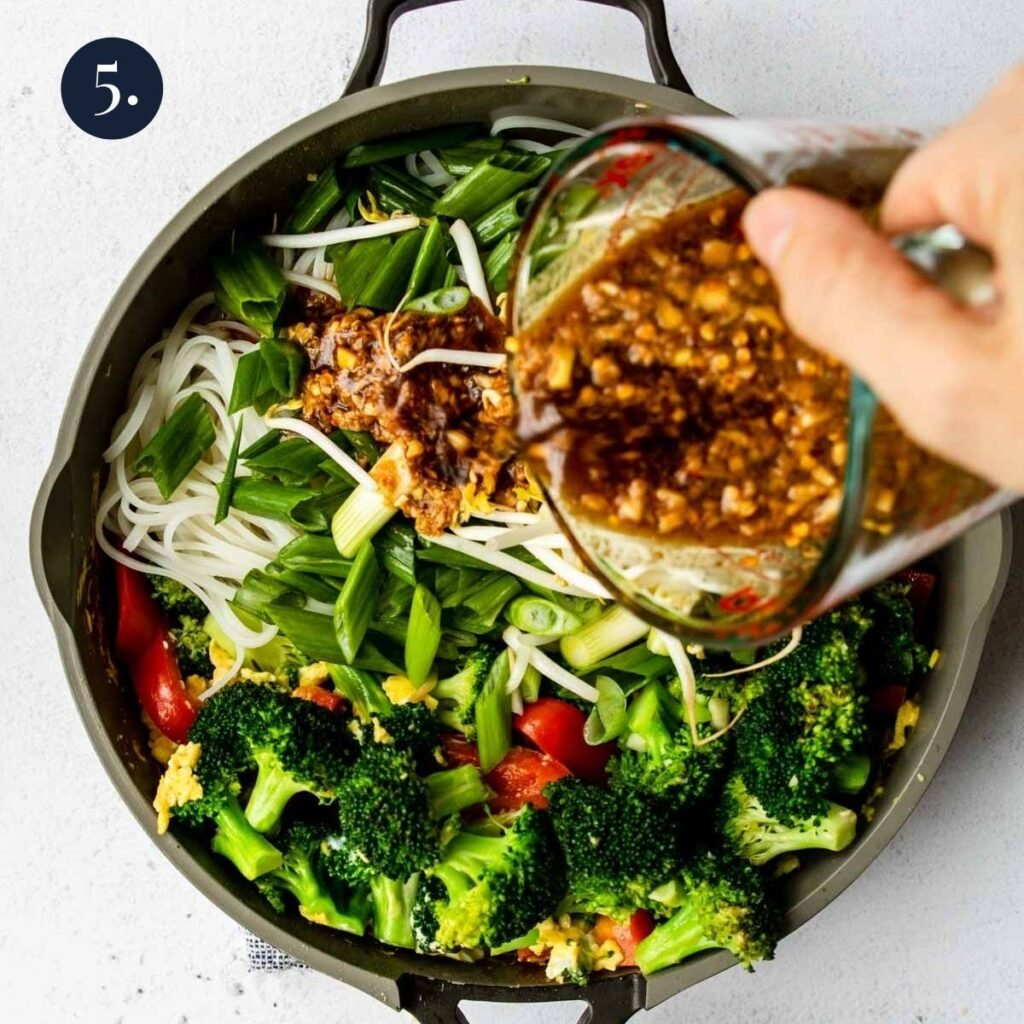 pouring Pad Thai sauce over veggies and noodles