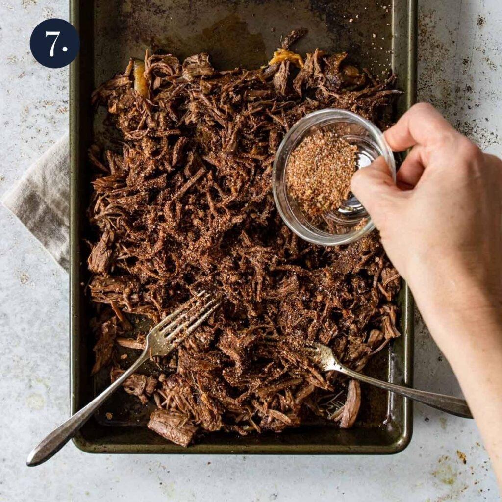 sprinkling seasoning on shredded beef