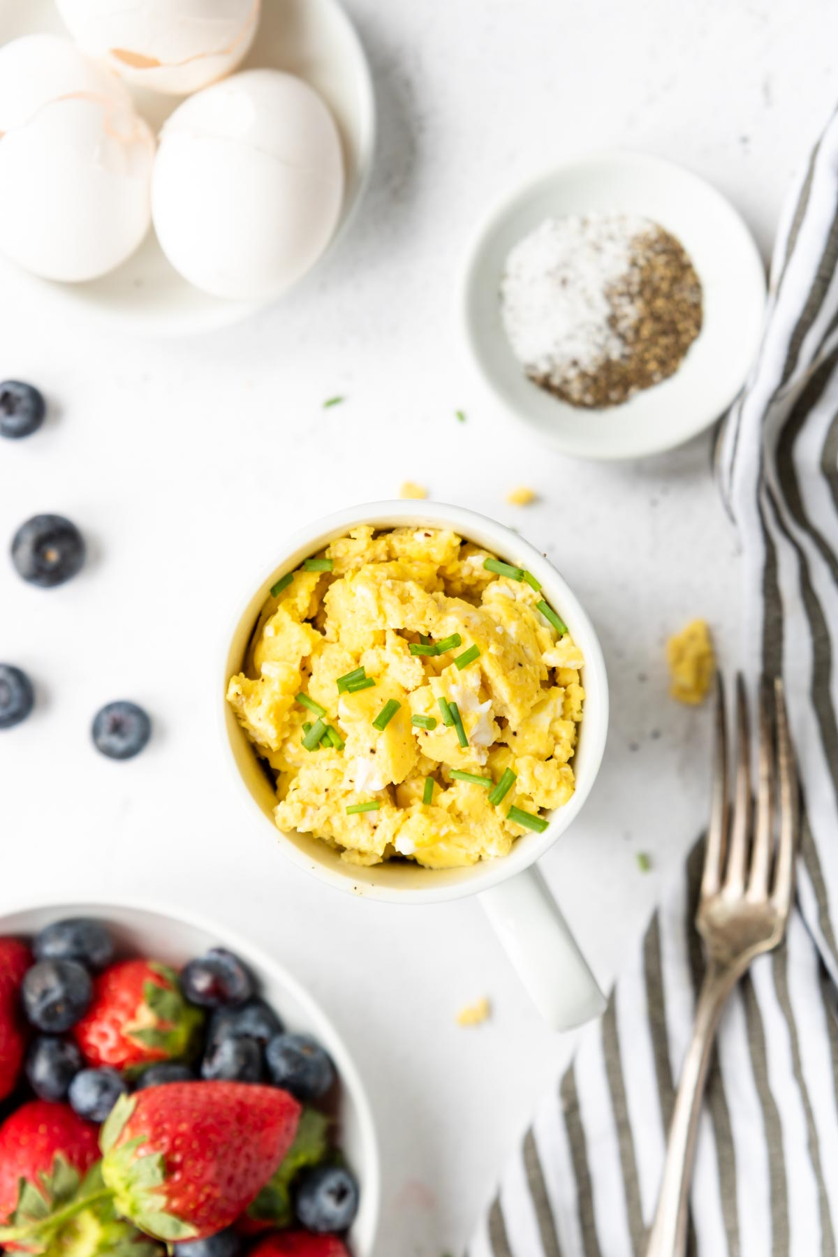 scrambled eggs in a white mug with strawberries and blueberries to the side