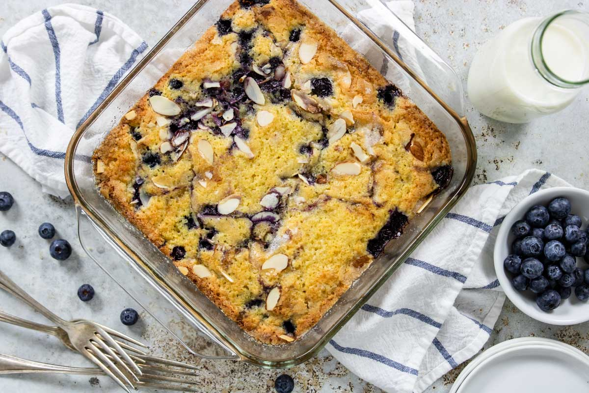 a lemon blueberry coffee cake on a table with milk and blueberries