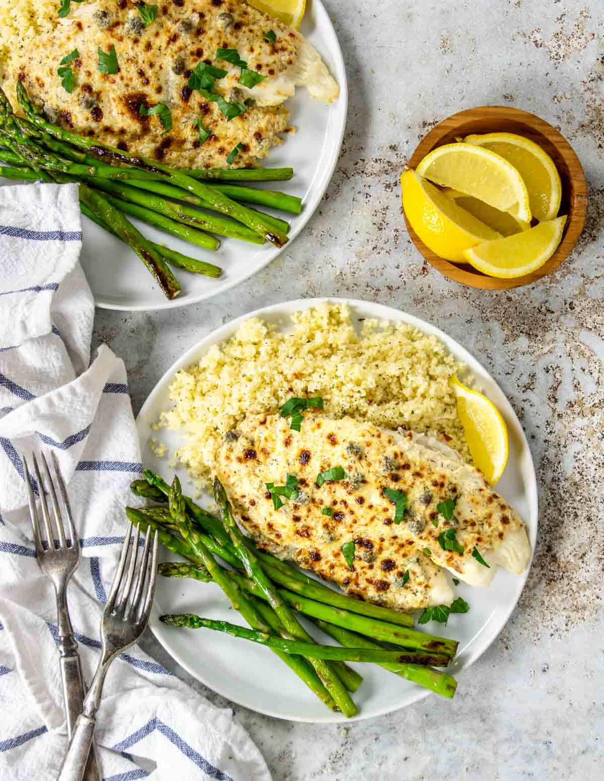 two dinner plates with parmesan tilapia, couscous and asparagus