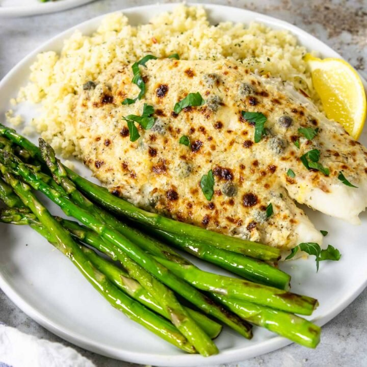 broiled parmesan tilapia on a plate with couscous and asparagus
