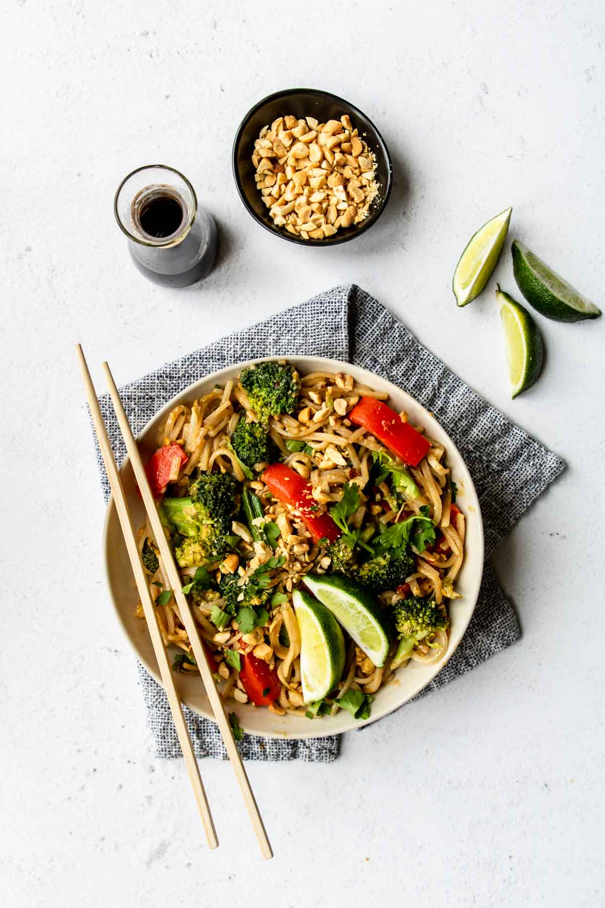 a bowl of Pad Thai with peanuts, limes and soy sauce to the side