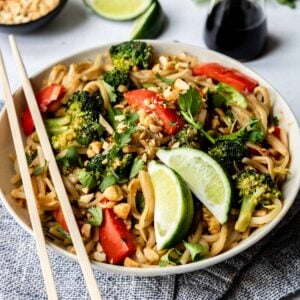 vegetable Pad Thai in a large bowl with chop sticks and limes