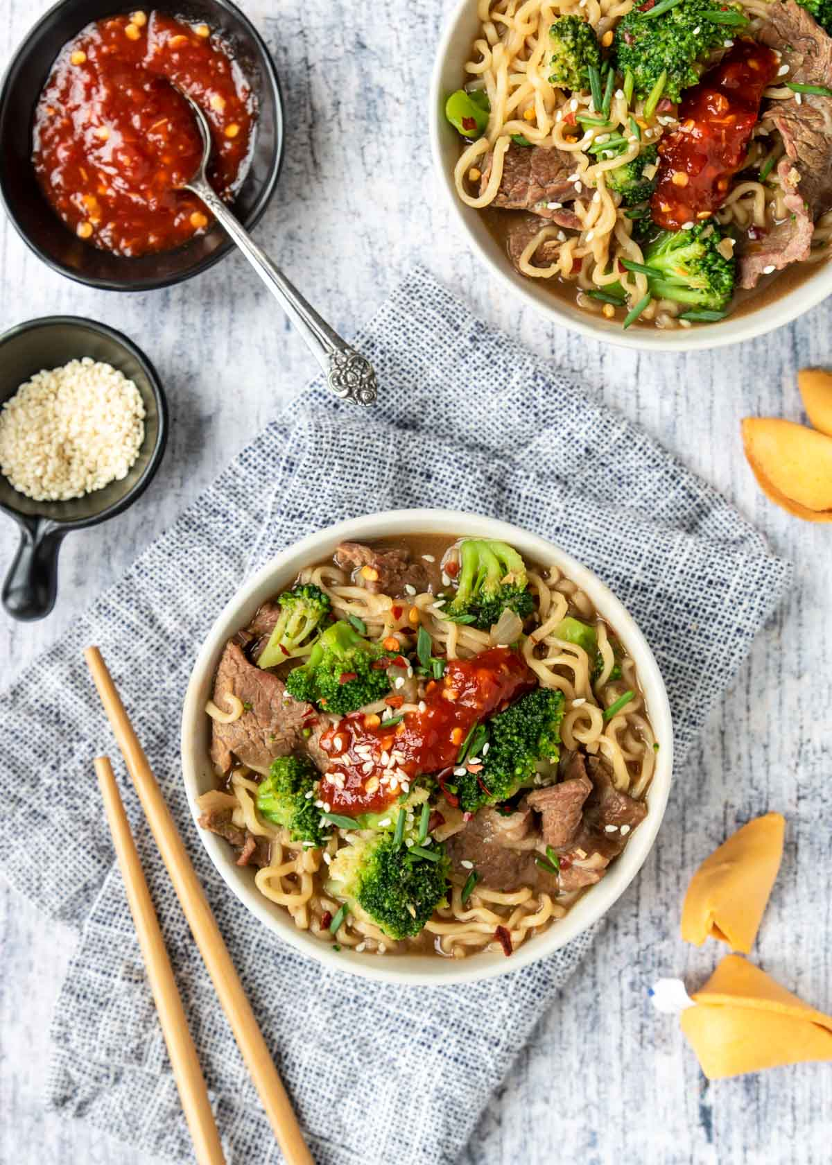 two bowls of beef ramen topped with chili paste and sesame seeds