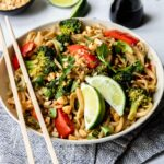 Vegetable Pad Thai in a white bowl with limes and chop sticks