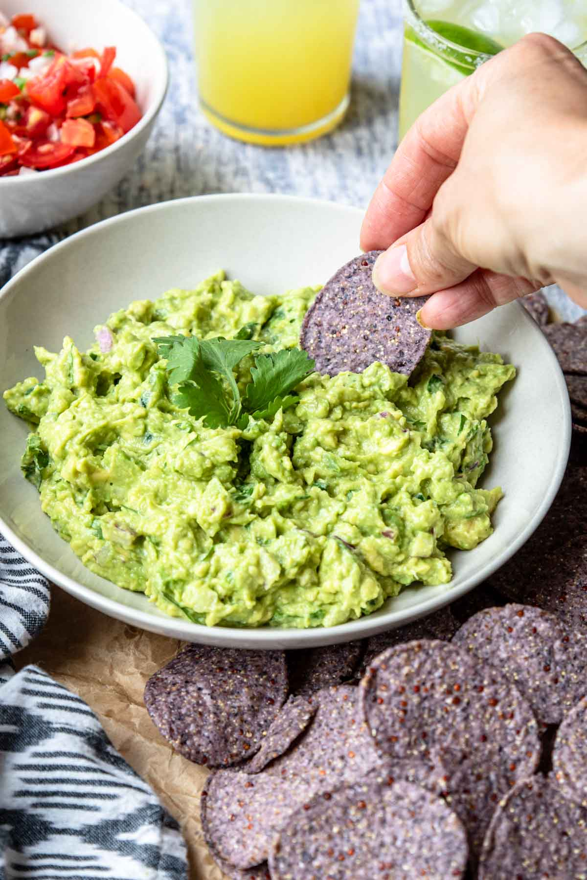 guacamole in a bowl being scooped with a blue corn tortilla chip