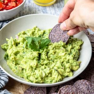 a bowl of fresh avocado guacamole with a chip dipping in